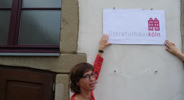 Das Provisorium hat ein Ende - Bettina Fischer, die Leiterin des Literaturhauses Köln, muss selber keinen Entwurf der Hinweistafel mehr halten...